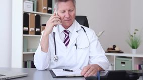Doctor chatting on his mobile phone stock footage