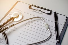Doctor check list with stethoscope and pen. Closeup Stock Photos