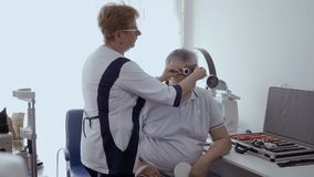Doctor check man`s eyesight with optical trial frame. Doctor check man`s sight with optical trial frame. Senior man has a bad eyesight and check it in stock video