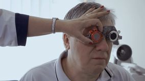 Doctor check man`s sight with optical trial frame. Senior man has a bad eyesight and check it in ophthalmologist in modern clinic stock footage