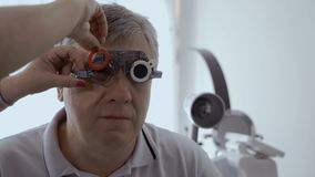 Doctor examine man`s sight with optical trial frame. Doctor check man`s sight with optical trial frame. Senior man has a bad eyesight and check it in stock video