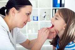 Doctor check throat of little girl.  Royalty Free Stock Images