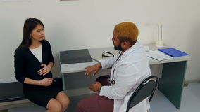 Doctor checking the belly of a pregnant woman stock video