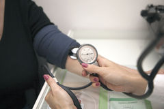 Doctor checking blood pressure. Doctors hand checking blood pressure stock photos