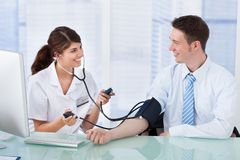 Doctor checking blood pressure of businessman in clinic Royalty Free Stock Photo