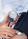 Doctor checking blood pressure of businessman Royalty Free Stock Photography