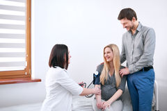 Doctor checking blood pressure of her pregnant patient. Young happy couple visiting doctor together. Female doctor checking blood pressure of a pregnant woman Stock Photos