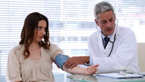 Doctor checking blood pressure of his patient Stock Photos