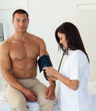 Doctor checking the blood pressure of a patient Royalty Free Stock Photos