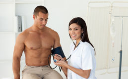 Doctor checking the blood pressure of a patient Royalty Free Stock Image