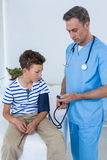 Doctor checking blood pressure of patient Stock Photos