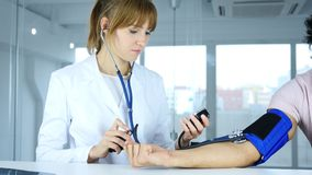 Doctor Checking Blood Pressure of Patient in Clinic. 4k , high quality Stock Photo
