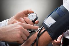 Doctor checking blood pressure of a patient Stock Image