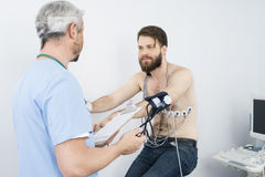 Doctor Checking Blood Pressure Of Patient On Exercise Bike Stock Images