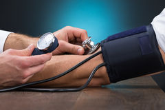 Doctor Checking Blood Pressure Of Patient At Table. Cropped image of male doctor checking blood pressure of patient at table royalty free stock photography