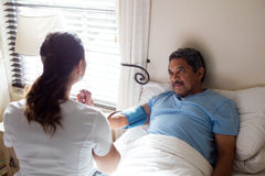 Doctor checking blood pressure of senior woman in bedroom Stock Image