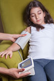 Doctor checking blood pressure of small beautiful middle eastern girl. Stock Images