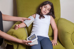 Doctor checking blood pressure of small beautiful middle eastern girl. Stock Image