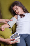 Doctor checking blood pressure of small beautiful middle eastern girl. Stock Photography