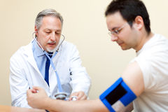 Doctor checking blood pressure Stock Photography