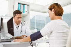 Doctor checking blood pressure of woman at medical office Royalty Free Stock Images