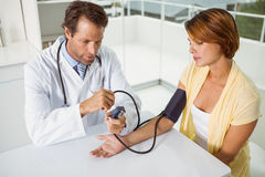 Doctor checking blood pressure of woman at medical office Royalty Free Stock Photography