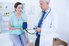 Doctor checking blood pressure of a young woman Stock Photos