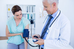 Doctor checking blood pressure of a young woman Royalty Free Stock Image