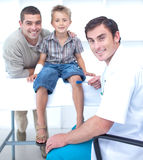 Doctor checking a boy reflexes Stock Photos