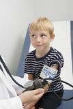 Doctor Checking Boy's Blood Pressure Stock Photography