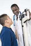 Doctor Checking Boy's Weight stock images