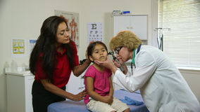 Doctor checking ears of sick child stock footage