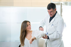 Doctor checking elbow with reflex round hammer to woman Royalty Free Stock Images