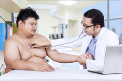 Doctor is checking a fat man Stock Photo