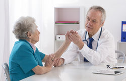 Doctor checking female patient's injured arm Royalty Free Stock Photos