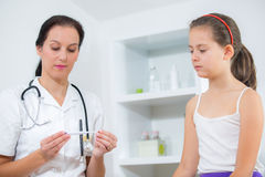 Doctor checking girl temperature. In doctor's office Stock Images