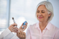 Doctor checking glucose level in diabetic patient. In clinic Stock Photos