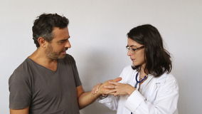 Doctor checking hand of a patient stock footage