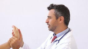 Doctor checking hand of a patient stock video