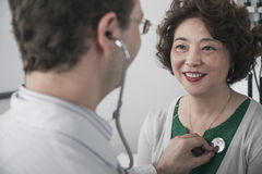Doctor checking heartbeat of a patient with a stethoscope Stock Photography