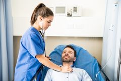 Doctor checking heartbeats of a patient. Pretty nurse using a stethoscope to examine a male patient in a hospital room Stock Photo
