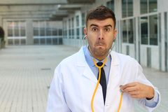 Doctor checking his own heartbeat with disbelief stock photography