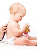 Doctor checking infant heart beat with stethoscope. Pediatrician examines little baby girl using a stethoscope to listen to baby's back checking heart beat Royalty Free Stock Photos