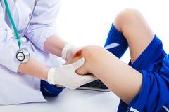 Doctor checking knee injury athlete, on white background. Studio Royalty Free Stock Photo