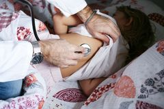 Doctor checking lungs of his patient. Close up of doctors hands using stethoscope to checking lung of little girl in the hospital stock images