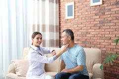 Doctor checking mature man`s pulse with fingers. At home royalty free stock photos