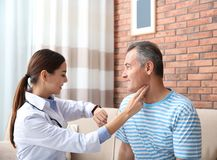 Doctor checking mature man`s pulse with fingers. At home stock images