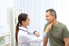 Doctor checking mature man`s pulse with fingers. In hospital stock photos