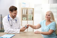 Doctor checking mature woman`s pulse with medical device royalty free stock image
