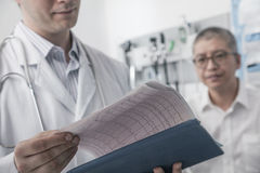 Doctor checking medical chart with patient in the background Stock Photos